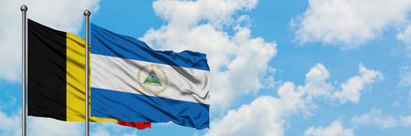 Belgium and Nicaragua flag waving in the wind against white cloudy blue sky together. Diplomacy concept, international relations.