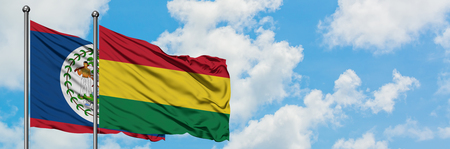 Belize and Bolivia flag waving in the wind against white cloudy blue sky together. Diplomacy concept, international relations. Imagens