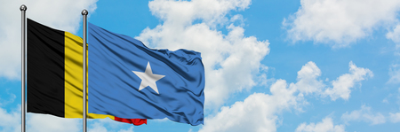 Belgium and Somalia flag waving in the wind against white cloudy blue sky together. Diplomacy concept, international relations. Stockfoto