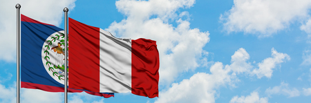 Belize and Peru flag waving in the wind against white cloudy blue sky together. Diplomacy concept, international relations. Stock Photo