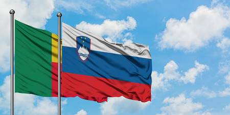 Benin and Slovenia flag waving in the wind against white cloudy blue sky together. Diplomacy concept, international relations.