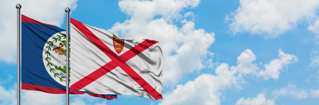 Belize and Jersey flag waving in the wind against white cloudy blue sky together. Diplomacy concept, international relations.