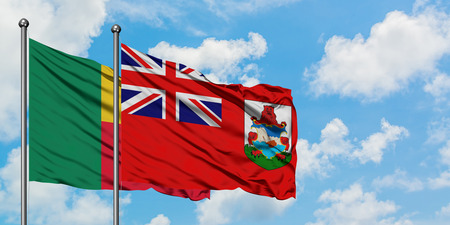 Benin and Bermuda flag waving in the wind against white cloudy blue sky together. Diplomacy concept, international relations.