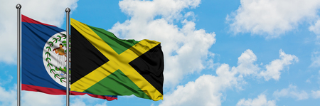 Belize and Jamaica flag waving in the wind against white cloudy blue sky together. Diplomacy concept, international relations. Stock Photo
