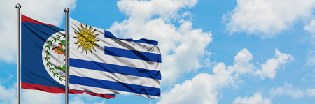 Belize and Uruguay flag waving in the wind against white cloudy blue sky together. Diplomacy concept, international relations.