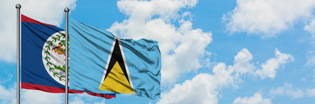 Belize and Saint Lucia flag waving in the wind against white cloudy blue sky together. Diplomacy concept, international relations.