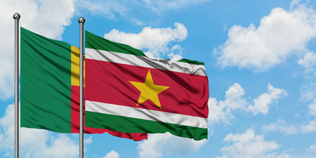 Benin and Suriname flag waving in the wind against white cloudy blue sky together. Diplomacy concept, international relations.