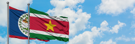 Belize and Suriname flag waving in the wind against white cloudy blue sky together. Diplomacy concept, international relations. Stockfoto
