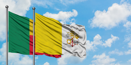 Benin and Vatican City flag waving in the wind against white cloudy blue sky together. Diplomacy concept, international relations.