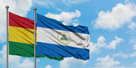 Bolivia and Nicaragua flag waving in the wind against white cloudy blue sky together. Diplomacy concept, international relations.