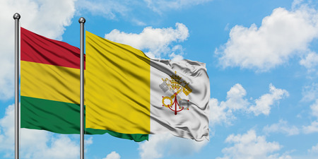 Bolivia and Vatican City flag waving in the wind against white cloudy blue sky together. Diplomacy concept, international relations.