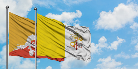 Bhutan and Vatican City flag waving in the wind against white cloudy blue sky together. Diplomacy concept, international relations.