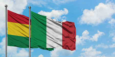 Bolivia and Italy flag waving in the wind against white cloudy blue sky together. Diplomacy concept, international relations. Фото со стока