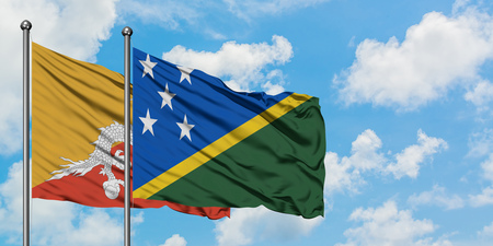 Bhutan and Solomon Islands flag waving in the wind against white cloudy blue sky together. Diplomacy concept, international relations.