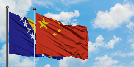 Bosnia Herzegovina and China flag waving in the wind against white cloudy blue sky together. Diplomacy concept, international relations.