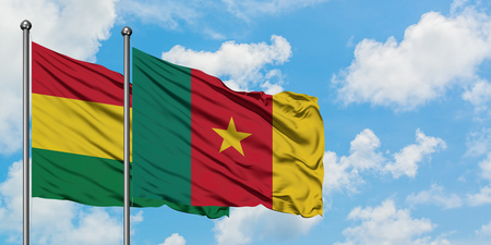 Bolivia and Cameroon flag waving in the wind against white cloudy blue sky together. Diplomacy concept, international relations. Stockfoto