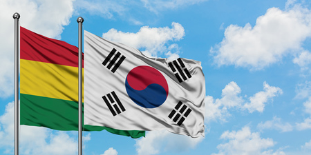 Bolivia and South Korea flag waving in the wind against white cloudy blue sky together. Diplomacy concept, international relations.