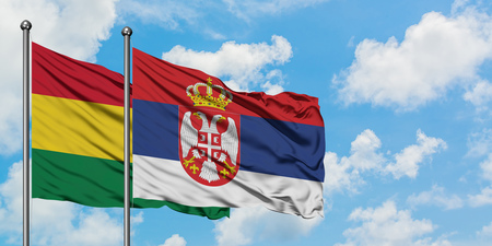 Bolivia and Serbia flag waving in the wind against white cloudy blue sky together. Diplomacy concept, international relations.