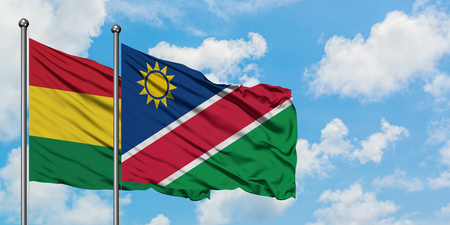 Bolivia and Namibia flag waving in the wind against white cloudy blue sky together. Diplomacy concept, international relations. Banco de Imagens