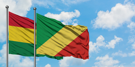 Bolivia and Republic Of The Congo flag waving in the wind against white cloudy blue sky together. Diplomacy concept, international relations. Фото со стока