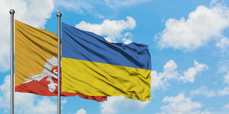 Bhutan and Ukraine flag waving in the wind against white cloudy blue sky together. Diplomacy concept, international relations.