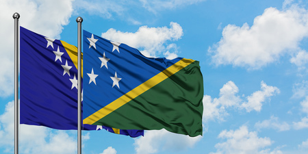 Bosnia Herzegovina and Solomon Islands flag waving in the wind against white cloudy blue sky together. Diplomacy concept, international relations.