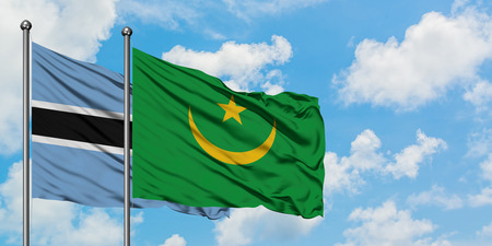 Botswana and Mauritania flag waving in the wind against white cloudy blue sky together. Diplomacy concept, international relations.