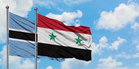 Botswana and Syria flag waving in the wind against white cloudy blue sky together. Diplomacy concept, international relations.