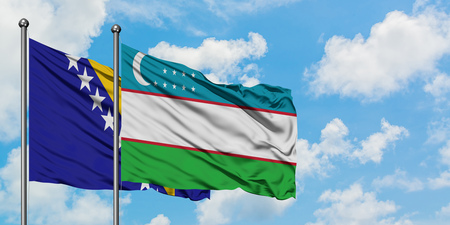 Bosnia Herzegovina and Uzbekistan flag waving in the wind against white cloudy blue sky together. Diplomacy concept, international relations.