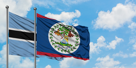 Botswana and Belize flag waving in the wind against white cloudy blue sky together. Diplomacy concept, international relations.