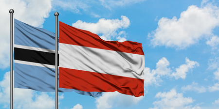 Botswana and Austria flag waving in the wind against white cloudy blue sky together. Diplomacy concept, international relations.