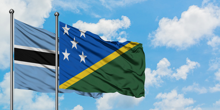 Botswana and Solomon Islands flag waving in the wind against white cloudy blue sky together. Diplomacy concept, international relations.
