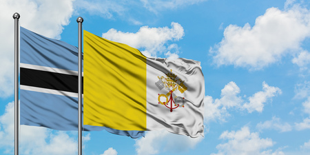 Botswana and Vatican City flag waving in the wind against white cloudy blue sky together. Diplomacy concept, international relations.
