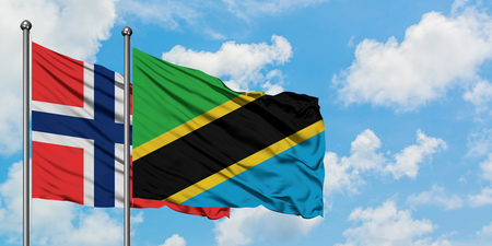 Bouvet Islands and Tanzania flag waving in the wind against white cloudy blue sky together. Diplomacy concept, international relations. Stock fotó