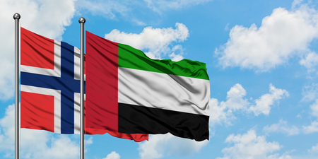 Bouvet Islands and United Arab Emirates flag waving in the wind against white cloudy blue sky together. Diplomacy concept, international relations.