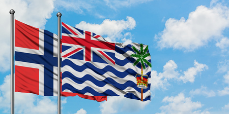 Bouvet Islands and British Indian Ocean Territory flag waving in the wind against white cloudy blue sky together. Diplomacy concept, international relations.