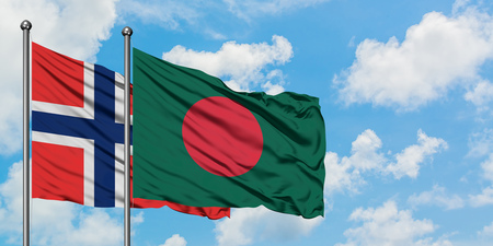 Bouvet Islands and Bangladesh flag waving in the wind against white cloudy blue sky together. Diplomacy concept, international relations. Foto de archivo