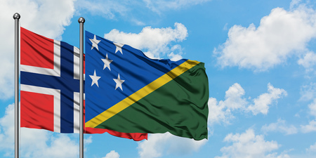 Bouvet Islands and Solomon Islands flag waving in the wind against white cloudy blue sky together. Diplomacy concept, international relations.