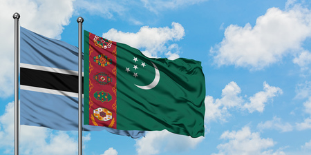 Botswana and Turkmenistan flag waving in the wind against white cloudy blue sky together. Diplomacy concept, international relations.