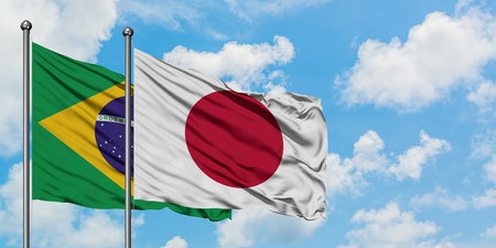Brazil and Japan flag waving in the wind against white cloudy blue sky together. Diplomacy concept, international relations.
