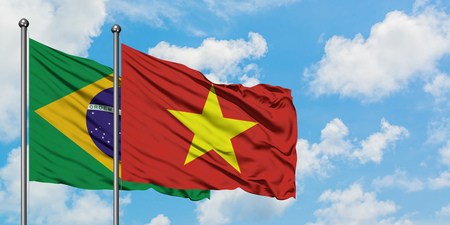 Brazil and Vietnam flag waving in the wind against white cloudy blue sky together. Diplomacy concept, international relations.