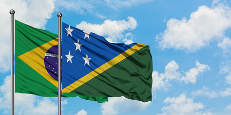 Brazil and Solomon Islands flag waving in the wind against white cloudy blue sky together. Diplomacy concept, international relations.