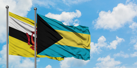 Brunei and Bahamas flag waving in the wind against white cloudy blue sky together. Diplomacy concept, international relations.