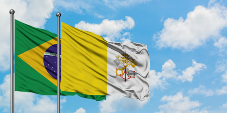 Brazil and Vatican City flag waving in the wind against white cloudy blue sky together. Diplomacy concept, international relations.