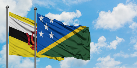 Brunei and Solomon Islands flag waving in the wind against white cloudy blue sky together. Diplomacy concept, international relations.