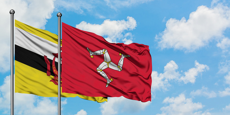 Brunei and Isle Of Man flag waving in the wind against white cloudy blue sky together. Diplomacy concept, international relations.
