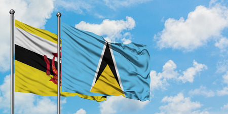 Brunei and Saint Lucia flag waving in the wind against white cloudy blue sky together. Diplomacy concept, international relations. Stock Photo