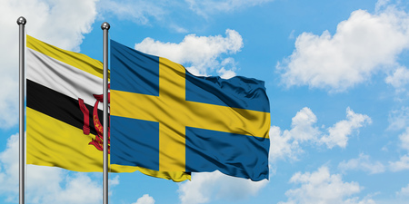 Brunei and Sweden flag waving in the wind against white cloudy blue sky together. Diplomacy concept, international relations. Stock Photo