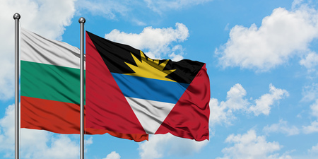 Bulgaria and Antigua and Barbuda flag waving in the wind against white cloudy blue sky together. Diplomacy concept, international relations.