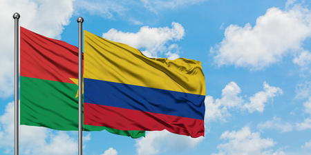 Burkina Faso and Colombia flag waving in the wind against white cloudy blue sky together. Diplomacy concept, international relations.